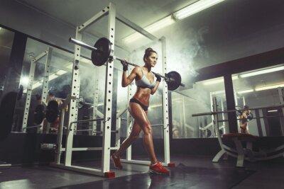 Fototapeta Młoda seksowna dziewczyna w siłowni robi przysiad na tle dymu
