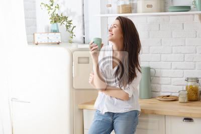 Fototapeta Młoda szczęśliwa kobieta pije kawę na kuchni w ranku