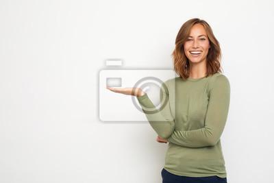 młoda szczęśliwa kobieta przedstawia twój produkt na thie tle