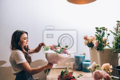 Fototapeta Młoda uśmiechnięta brunetki kobiety biznesowej kobiety kwiaciarnia tworzy pięknego bukiet kolorowi różni kwiaty w nowożytnym wewnętrznym kwiecistym sklepie. Widok z boku