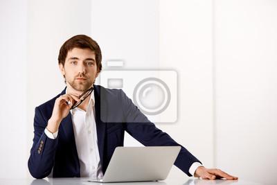 Młody biznesmen siedzi przy biurku