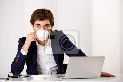 Młody biznesmen siedzi przy biurku i picia
