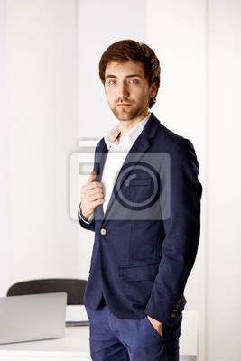 Młody biznesmen stojący przy biurku