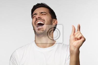 Fototapeta Młody człowiek demonstruje coś bardzo małego z dwoma palcami