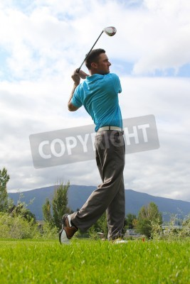 Fototapeta Młody golfista jazdy z drewna przed pochmurne niebo