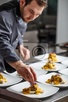 Fototapeta Młody kucharz przygotowuje posiłki