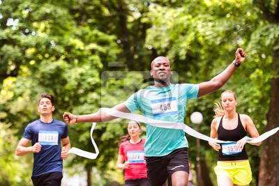 Młody mężczyzna biegnie w tłumie przekraczającym linię mety.