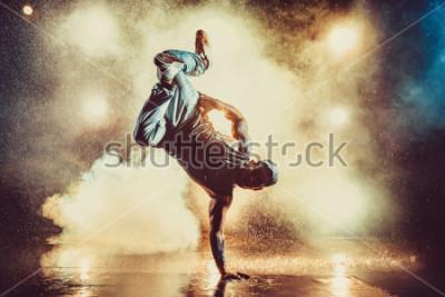 Fototapeta Młody mężczyzna cool break dance w klubie ze światłami, dymem i wodą. Tatuaż na ciele.