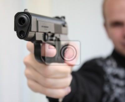 Młody mężczyzna na celu z pistoletu w ręku
