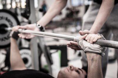 Fototapeta Młody mężczyzna podnosząc sztangę na siłowni z instruktorem.