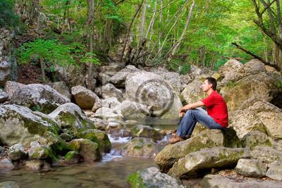 Młody mężczyzna siedzi na górze rzeki