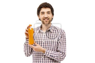Młody przystojny mężczyzna wesołej pokazujący plastikowe butelki z pomarańczowym b