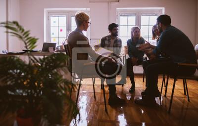 Fototapeta Młodzi ludzie z problemami mającymi dyskusję podczas wspólnego przebywania na specjalnej terapii grupowej.