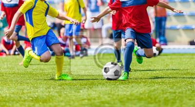 a4c1d07a4 Fototapeta Młodzież mecz piłka nożna. Dzieci bawiące się mecz piłki nożnej  na polu sportowym.