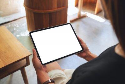 Fototapeta Mockup image of a woman holding digital tablet with blank white desktop screen