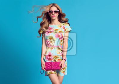 Fototapeta Moda. Blond kobieta w mody pozie. Młoda piękna dama w kwiecistej sukni Dmuchanie wargi. Modna moda Hairstyle, Glamour Pink Clutch. Zabawna dziewczyna, strój wiosna lato