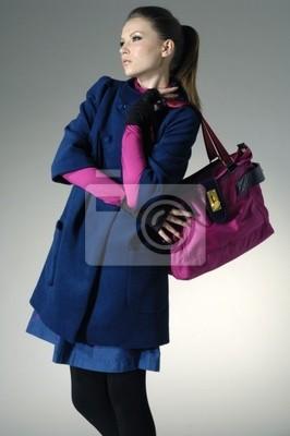 Moda dziewczyna z torebka stwarzających w świetle tle