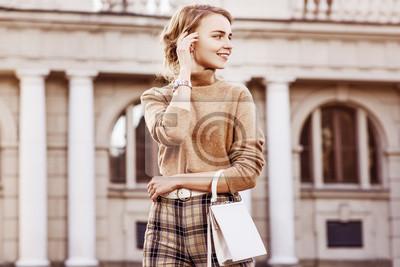 Fototapeta Moda na zewnątrz portret młodej szczęśliwej uśmiechniętej damy w modnym beżowym golfie, spodniach w kratę z wysokim stanem, zegarku na nadgarstku, pasie, noszących małą białą torbę, pozujących na ulic