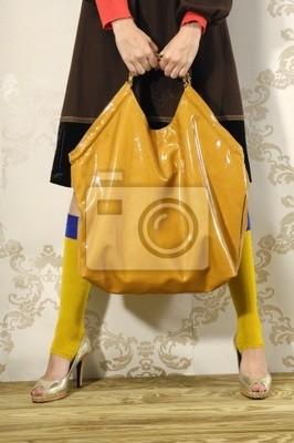 Model trzyma skórzaną torbę w dłoni.