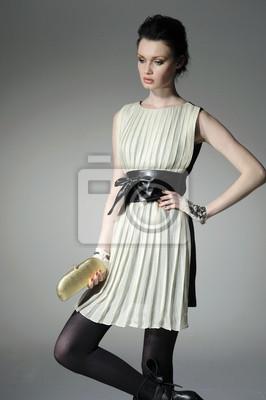 modelka trzyma małą torebkę na jasnym tle