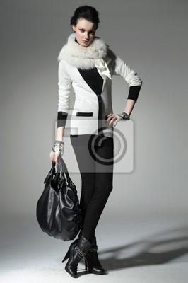 , Modelka w jesienno / zimowe ubrania trzyma torebkę stwarzających