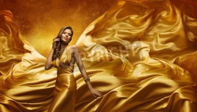 Fototapeta Modelka w sukni złota, piękna kobieta stwarzających na latający macha Cloth, Dziewczyna z żółtym dynamiczny tkaniny jedwabne