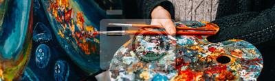 Fototapeta Modern fine art school. Female painter holding colorful palette and paintbrushes over abstract artwork.