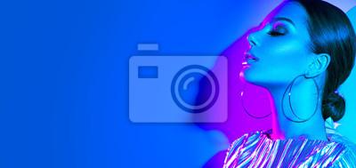 Fototapeta Mody modela brunetki kobieta w kolorowych jaskrawych neonowych światłach pozuje w studiu. Piękna seksowna dziewczyna, modny świecący makijaż, metalowe srebrne usta