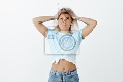 Moja głowa wyleci z informacji. Zmęczona, zmęczona, śliczna i zabawna kobieta w stylowo przyciętym topie i dżinsach, dmuchająca w kosmyk włosów z twarzy, dotykająca głowy, dąsana, przygnębiona i wycze