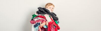 Fototapeta Mommy little helper. Adorable funny child arranging organazing clothing. Kid holding messy stack pile of clothes things. Home chores housework for kids. Web banner header.