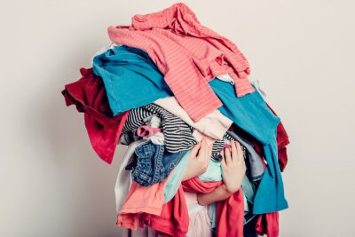 Fototapeta Mommy little helper. Cute Caucasian girl sorting clothes. Adorable funny child arranging organazing clothing. Kid holding messy stack pile of clothes, things. Home chores housework.