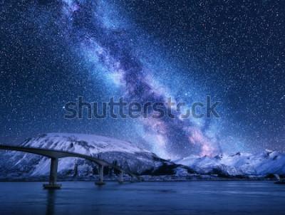 Fototapeta Most i gwiaździste niebo z Drogą Mleczną nad ośnieżonymi górami odbijanymi w wodzie. Nocny krajobraz z drogą, zaśnieżone skały, fioletowe niebo z gwiazdami i mleczną drogą, morze. Zima na Lofotach w N
