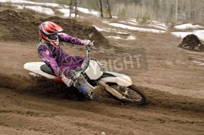 Fototapeta Motocross rider inclination the bike turns point-blank of sand