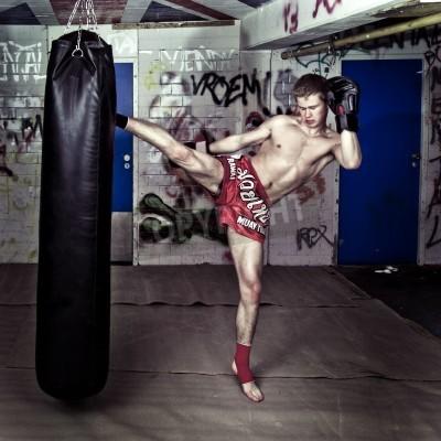 Fototapeta Muay Thai fighter dając wysokie kopnięcie podczas rundy ćwiczeń z workiem bokserskim w piwnicy miejskiej