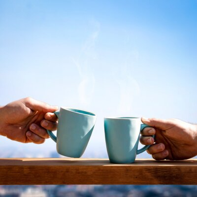 Mug of blue colors with tea or coffee and city landscape with blue sky.