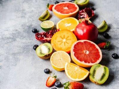 Fototapeta Multicolored seasonal healthy natural fruit composition with persimmon, blueberries, orange, kiwi, strawberries, grapefruit, pomegranate, orange slices.