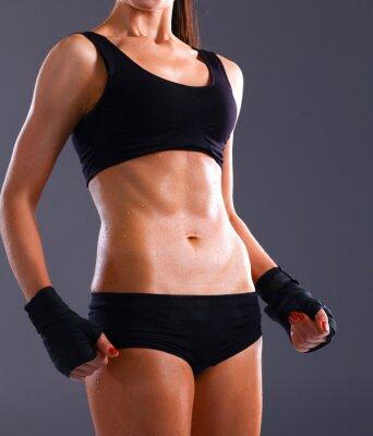 Fototapeta Muscular młoda kobieta stojąca na szarym tle