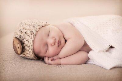 Fototapeta najmniejszy noworodek świata w czapeczce z wielkim guzikiem