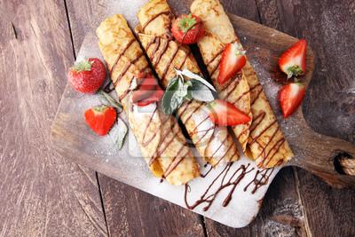 Naleśniki z dżemem, jagodami i cukrem pudrem. Domowe naleśniki, pyszne śniadanie.