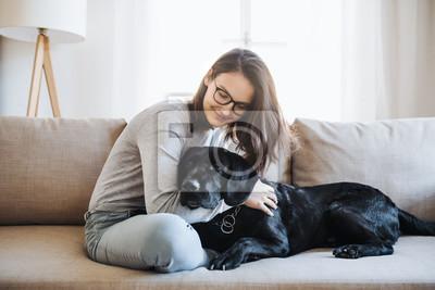 Fototapeta Nastoletnia dziewczyna siedzi na kanapie w pomieszczeniu, grając z psem.