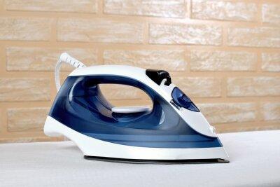 Fototapeta New modern electric steam iron on ironing board