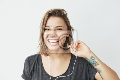 Nice young girl in headphones laughing looking at camera over white background.