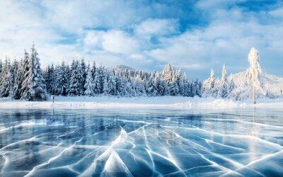 Fototapeta Niebieski lód i pęknięcia na powierzchni lodu. Zamarznięty jezioro pod niebieskim niebem w zimie. Wzgórza sosnowe. Zimowy. Karpacki, Ukraina, Europa.