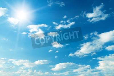 Fototapeta Niebieskie niebo z chmurami i słońcem.