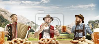 Fototapeta Niemcy, Bawaria. Szczęśliwi uśmiechnięci śpiewaccy mężczyzna z piwem ubierali w tradycyjnym Austriackim lub Bawarskim kostiumu z Bawarskimi preclami przeciw Alpejskiemu górskiemu krajobrazowi. oktober