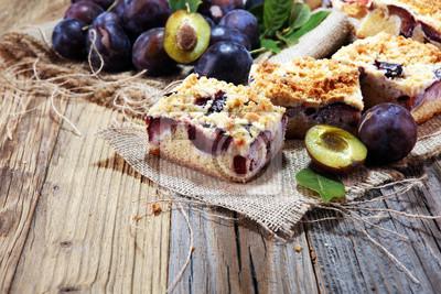 Nieociosany śliwka tort na drewnianym tle z śliwkami wokoło.