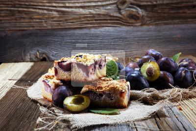 Nieociosany śliwkowy tort na drewnianym tle z śliwkami wokoło.