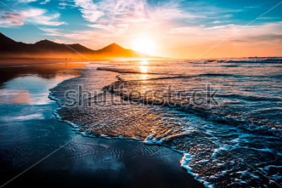 Fototapeta Niesamowity zachód słońca na plaży z niekończącym się horyzontem i samotnymi postaciami w oddali oraz obsługiwanymitmi spienionymi falami. Wulkaniczne wzgórza w tle.