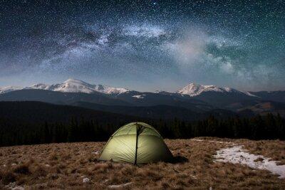Fototapeta Nocne kempingi. Oświetlony namiot turystyczny pod pięknym nocnym niebem pełnym gwiazd i mlecznej drogi. Na tle pokryte śniegiem góry i lasy