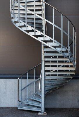 Fototapeta Nowoczesne metalowe schody kręcone powyżej ciemnoszarym ścianie
